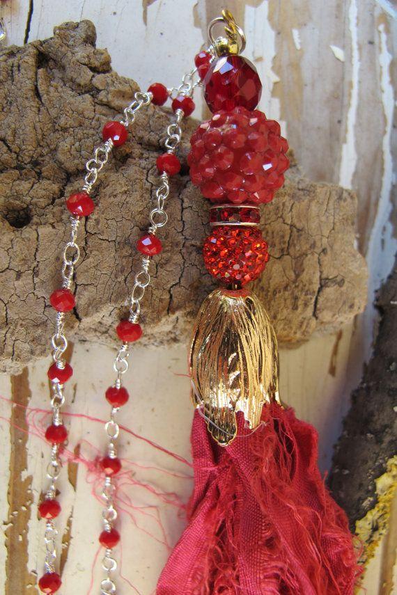 Lunga collana rossa in argento 925 e perline rosse di corallo. La collana ha perline in strass, perla ceramica, e nappina rossa in tessuto indiano originale sari. Perfetta per essere indossata con ogni stile di abbigliamento, e in ogni occasione.