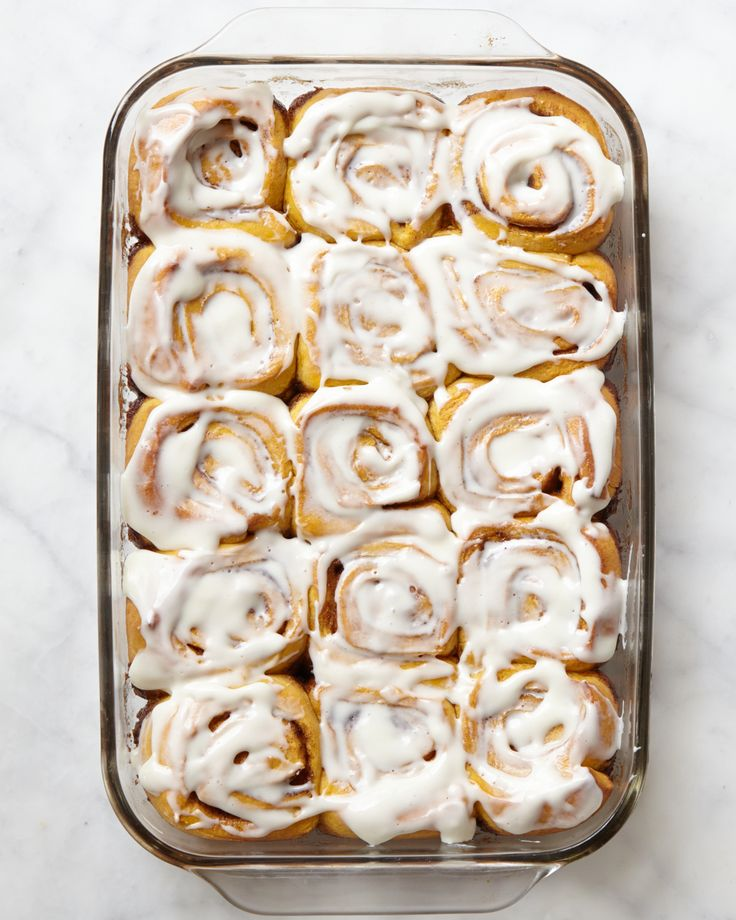 Pumpkin-enriched yeast dough swirls around a cinnamon-sugar filling; cream cheese frosting cloaks the top of each roll.