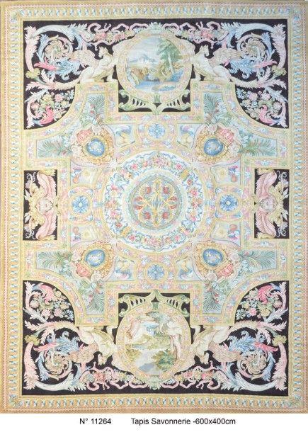 Important Tapis de Style Savonnerie (Style XVIIème siècle = Louis XIV), 20ème siècle, à décor de médaillon central géométrique, encadré de cartouches incrustés de paysage et orné d'une couronne de fleurs… - Jonquet - 19/01/2016