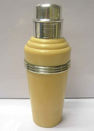 "1930's Epns and Bakelite Recipe Cocktail Shaker  ""The Master Incolor Cocktail Shaker"". This is the ivory coloured example from the master incolor series of art deco recipe cocktail shakers made from bakelite and silver plate. It has a revolving recipe top, internal strainer and pourer. The top cup serves as a drinks measure and is marked inside with concentric rings. Height 29 cms. Marked ""Made in England. Patent pending""."