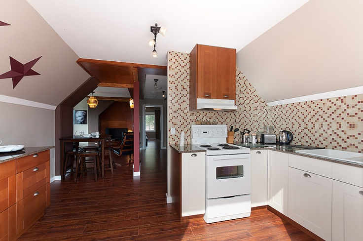 The kitchen fits perfectly in a sensible layout where the cooking area is easily maneuverable and nicely accented with a glass-tile mosaic backsplash.  #Vancouver #CommercialDrive #Kitchen #Hotel