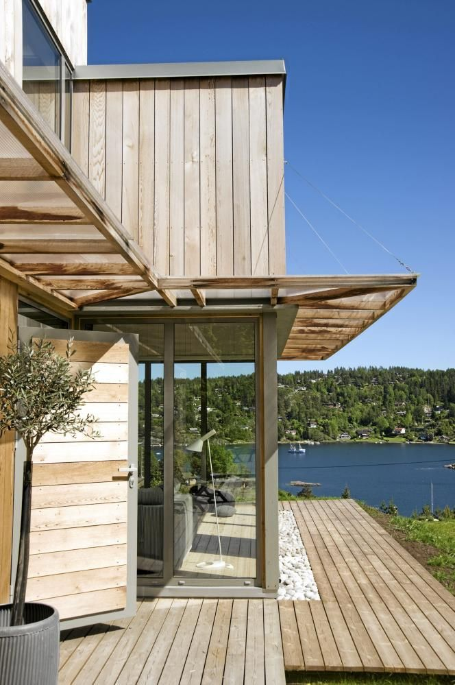 ARKITEKTTEGNET: Den nyfunksjonalistiske hytta er tegnet av sivilarkitekt Tore Koxvold i Helggelund og Koxvold.  De store vinduene vender ut mot sj�en. For � skjerme mot sola er det montert skyvbare skodder av liggende spileverk foran vinduene. Vindusomrammingen er i vedlikeholdsfri aluminium, i fargen Betonggrau, fra Sch�co. Fasaden er i kanadisk sedertre som er vedlikeholdsfri.