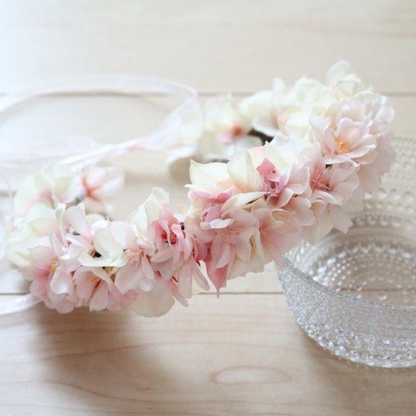 ◆ story ◆きれいな桜の木の下で記念写真をパシャリ。お子さまと一緒の可愛いロケーションフォト撮影のアイテムに桜の花冠はいかがでしょうか?春生まれのお子さまのお誕生日にもおすすめです♪淡く柔らかい雰囲気の桜に合わせ、クリーム・ピンクのアジサイでまとめました。大人用も制作可能ですので、ママとお揃いもいいですね。ご希望の場合はお問合せください。サイズをご確認のうえ、調整が必要そうな場合もお問合せいただければ個別にご対応させていただきます。◆ point ◆受注制作とさせて頂いておりますので、仕入れ状況により多少資材が変更になる場合がありますが、同じイメージでお作りしますので、あらかじめご了承ください。お花をひとつひとつワイヤリングして、ブラウンのテープで巻き留めています。ワイヤーは飛び出ないように留めていますので危険は少ないとは思いますが、ご使用時は大人の方が見て頂くようにお願いいたします。◆ photo ◆ ①淡いピンクが女の子らしさ、春らしさ満点です。 ②反対のアングルで取りました。 ③リボンも薄いピンク色です。◆ materials ◆ アーティフィシャルフラワー ・桜…