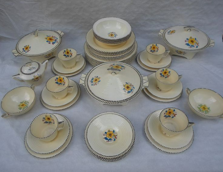 An early 1930s Crown Ducal part dinner service, designed by Charlotte Rhead in the 3122 pattern, the decoration of printed floral sprays on a cream ground with black stitch edging, on the 'Cotswold' shape tableware, comprising covered tureens, trios, soup bowls, dinner plates, side plates and others