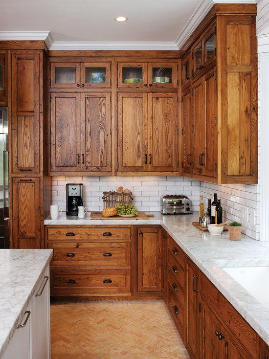 Reclaimed Chestnut cabinetry reaches all the way to the ceiling in a door over door configuration    Photo Credit   Crown Point Cabinetry #kitchendesign