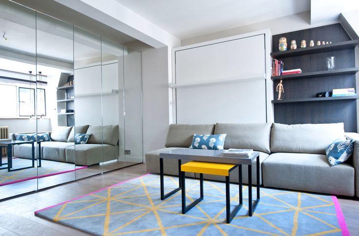 Обратите внимание на палитру интерьера. Бело-серые нейтральные оттенки разбавляет ковёр с яркими полосками, оттеночно согласуясь с журнальными столиками. Теперь этот интерьер серым никак не назовёшь.