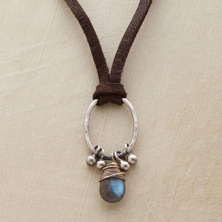Knotted on soft suede, a hammered sterling oval suspends a pear-shaped labradorite pendant and silver barbell beads. Sterling silver hook clasp.
