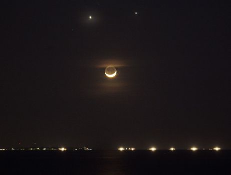 12.08.08: conjunction of venus, jupiter, and the moon. people in asia witnessed a smiley face (above, photographed from manila, philippines), while skywatchers in the united states saw a frown.