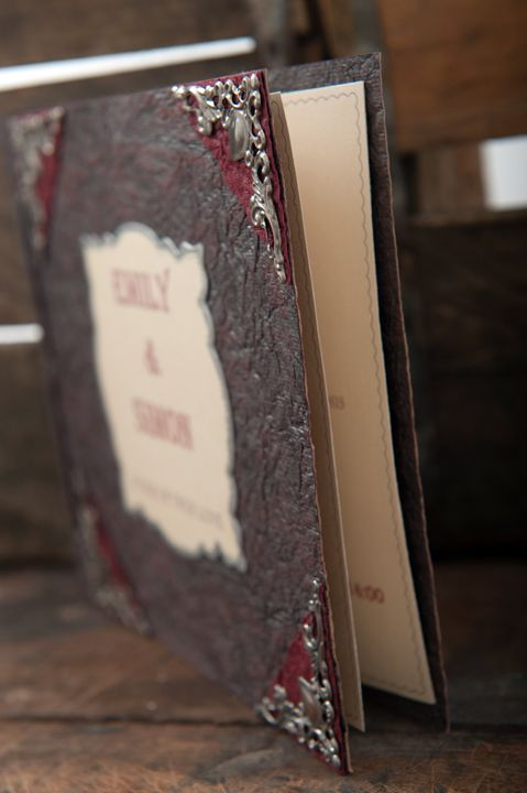 Antique, Gothic book styled wedding invitation with metal corner details, bound with thin leather thong down the spine.