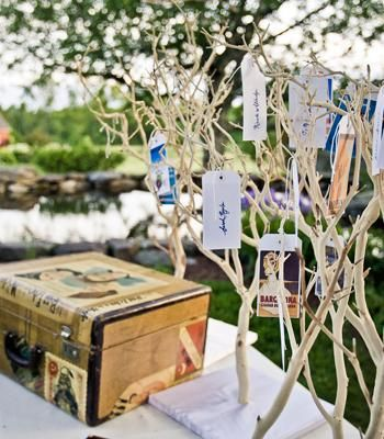 vintage luggage tags as place cards hanging from branches displayed with a vintage suitcase