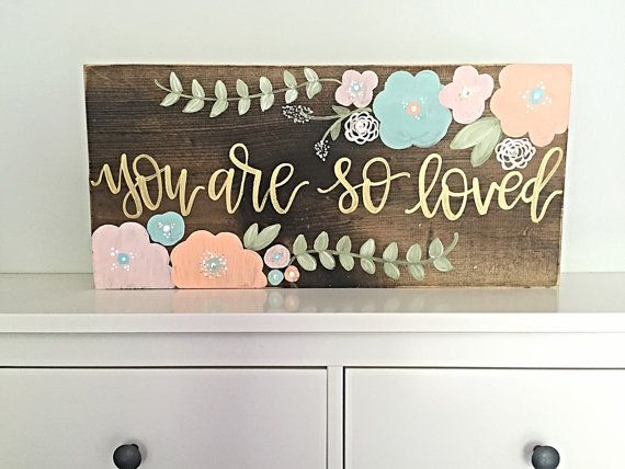 Size: 24 wide by 12 tall  Details: This listing features a stained wood background with lightly distressed edges. Hand painted flowers featured in mint/light blue, coral, and blush pink with gold and white accents and gold hand painted lettering featuring the quote you are so loved Options: We would be more than happy to create a custom version of this sign for you! Include your details at checkout in the notes area or message us prior to ordering to discuss your ideas! *Hanging hardware...
