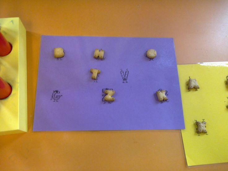 Letterkoekjes spel - Om de beurt een koekje nemen uit een zakje en kijken of de letter op jouw kaart staat.