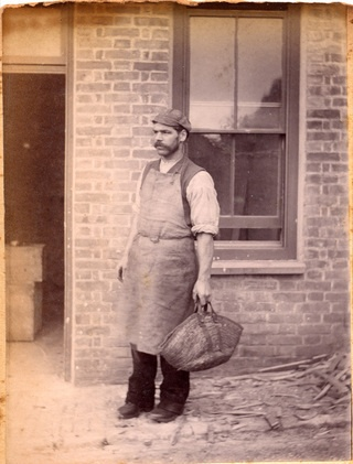 A photograph of an unknown man, who, judging by his full apron, cap and rolled up shirt sleeves, could be a carpenter. He holds a large tool bag and stands in front of the Stables and Mews within the grounds of Penlee House. - Collections - Penlee House Gallery and Museum Penzance Cornwall UK