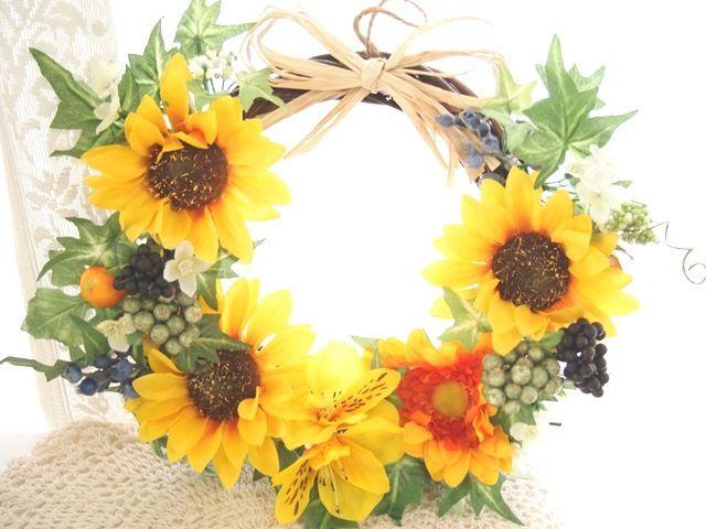 向日葵が印象的な夏満喫華やかリースです。眺めているとビタミンカラーで元気いっぱいハッピーな気分になれますね。グリーンと黄色のお花たちは可愛くてにっこり癒されます。木の実もいっぱいナチュラルなラフィアも可愛いのポイントです。ナチュラルなテイストですので玄関...