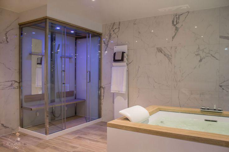 Maatwerk klassiek-chique badkamer met grote wandtegels en kerlite tegels met hout-look op de vloer. Verder heeft deze badkamer een ruime jacuzzi met LED verlichting in het bad en waterval kraan. Daarachter een dubbele douchecabine met zitbank en handdouche #badkamerstudio #badkamerstudiobreda #badkamerstudioutrecht