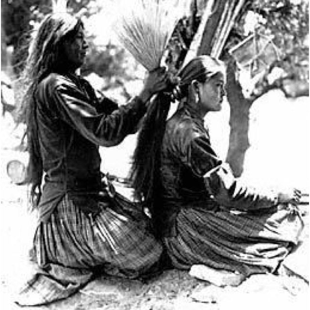 Navajo girl getting her hair done using a Navajo hairbrush made of dry grass strands.