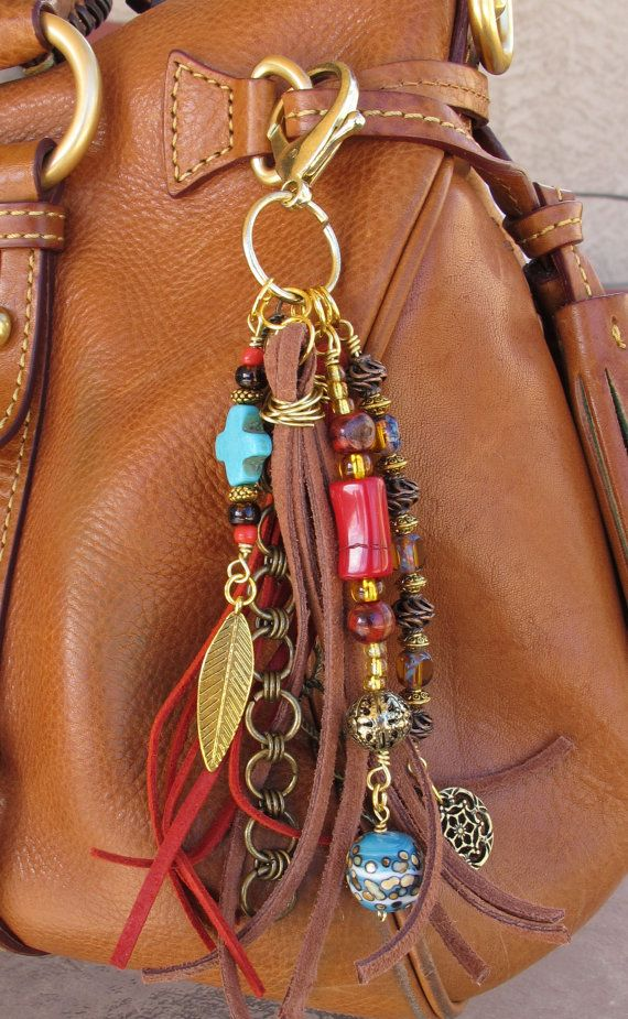 This handmade tassel charm can be used on your purse, backpack, zipper, wherever youd like to add some charm! Its made up of antiqued brass chain, brass charms, and different types of beads - gold filled, copper, glass, agate, wood, and other natural stone beads. The suede tassels are brown and red in color. It is approximately 7 long.