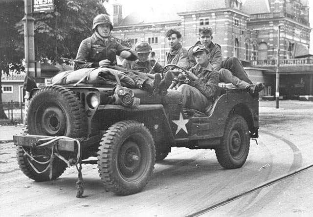 Three grenadiers of the 9. Waffen-SS Panzer Division Hohenstaufen in a Willys MB jeep with two British 1st Airborne Division POW's, Netherlands, …