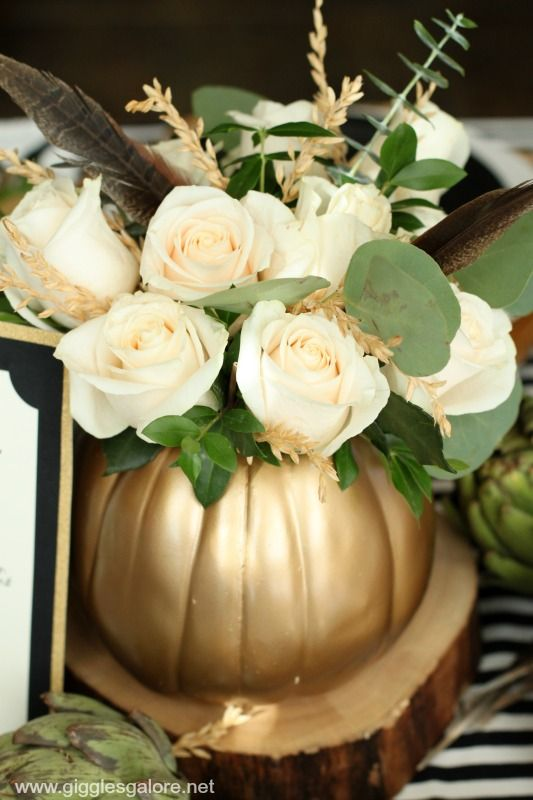 Beautiful floral arrangement with white roses, eucalyptus, and feathers inside a gold pumpkin.