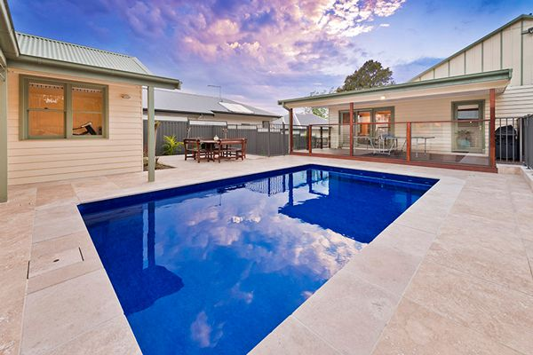 Small rectangular swimming pool in Heathmont by Albatross Pools measuring 6.0m x 3.5m featuring soothing spa jets along the comfort seat. Central to a table tennis deck, an alfresco area, a netball and basketball practice area and a putt putt zone, the small pool features the darkest Aqualux Bahama Pool Interior and is surrounded by Travertine Tiles.