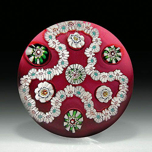 Antique Clichy trefoil garland paperweight, with a white millefiori garland, surrounding four spaced complex canes and looped around three green and white canes
