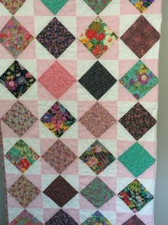 This quilt features a variety of florals in the diamonds surrounded by pink and white checks.