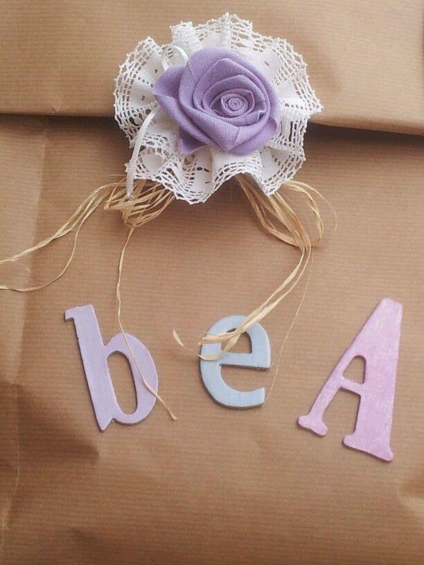 Confezione regalo in carta da pacchi, decorata con lettere fustellate, rosa in fettuccia e pizzo
