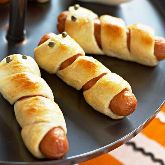 Mummy Dogs  Hot dogs are a party favorite and will become the star of a Halloween buffet when given this mummy wrap treatment using refrigerated breadsticks.To make, follow these steps:1.	Stretch uncooked breadsticks to 12 inches.2.	Wrap dough around hot dogs; be sure to let the meat show slightly through the wraps.3.	Press in capers for eyes.4.	Bake until bread is golden brown (about 12 minutes). Serve with ketchup and mustard