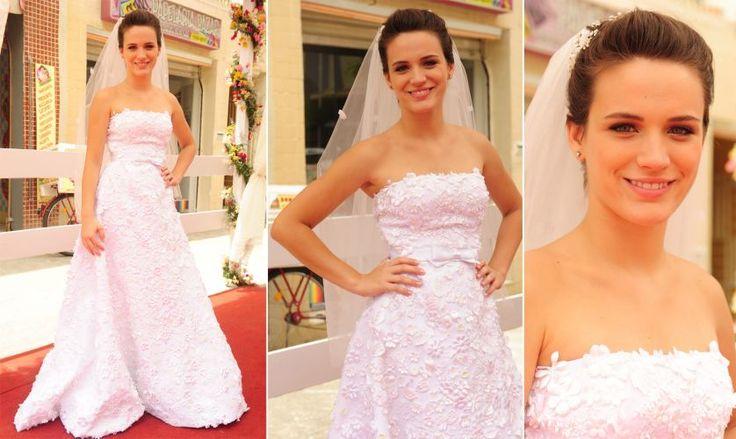 """Para uma cerimônia de casamento diurna na novela """"Passione"""", a noiva Fátima (Bianca Bin) usou um vestido tomara-que-caia todo coberto com aplicações florais que formavam um desenho em alto-relevo e com a cintura marcada por um laço discreto"""