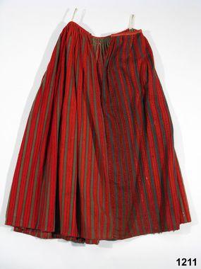 Kjol av halvylle i treskaftad kypert, varp av oblekt lingarn dold av inslaget av entrådigt ullgarn, randig i rött och grönt, de röda rändern...