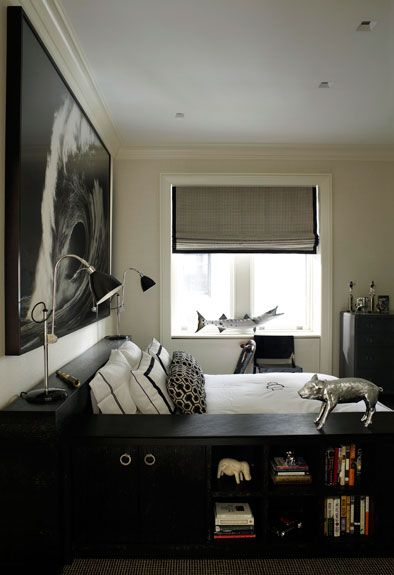 Suzie: David Kleinberg Design Associates - Chic boy's bedroom with tan walls paint color, gray roman shades with black velvet ribbon trim, white horel bedding with black border, silver pig bank and black bookshelves.