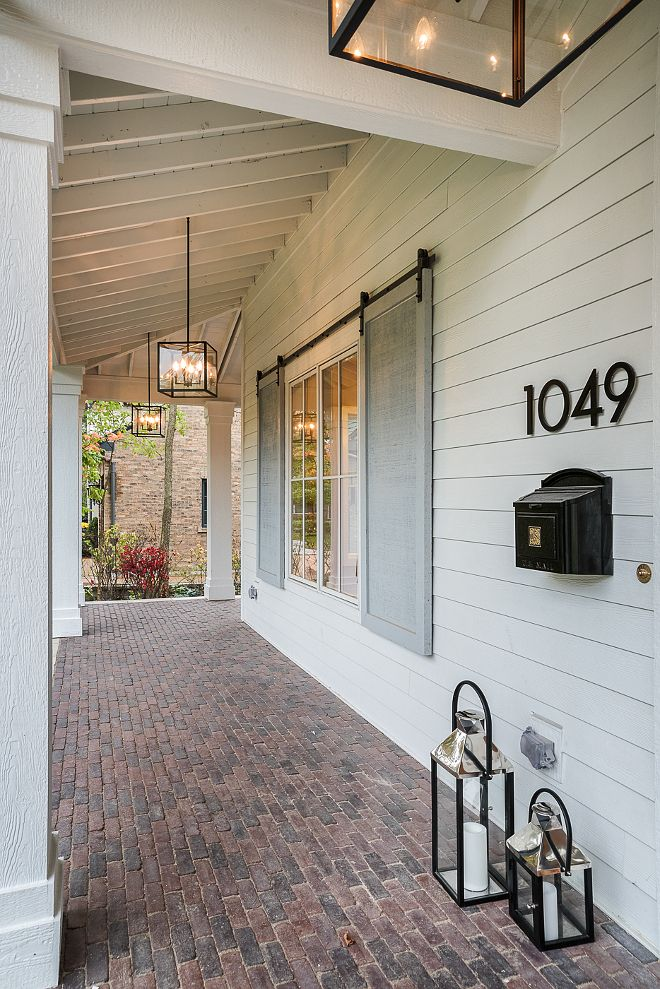 Brick Porch. Long porch with brick floor tile and grey shutters with barn door hardware. Dream home