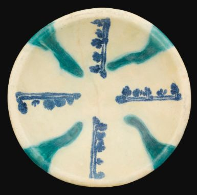 An Abbasid Calligraphic pottery Bowl, Iraq, 9th/10th century the bowl of shallow rounded form with a slightly everted lip on a low foot, with four centrifugal copper green splashes on an opaque white glaze between cobalt blue foliate inscriptions 24cm. diam.