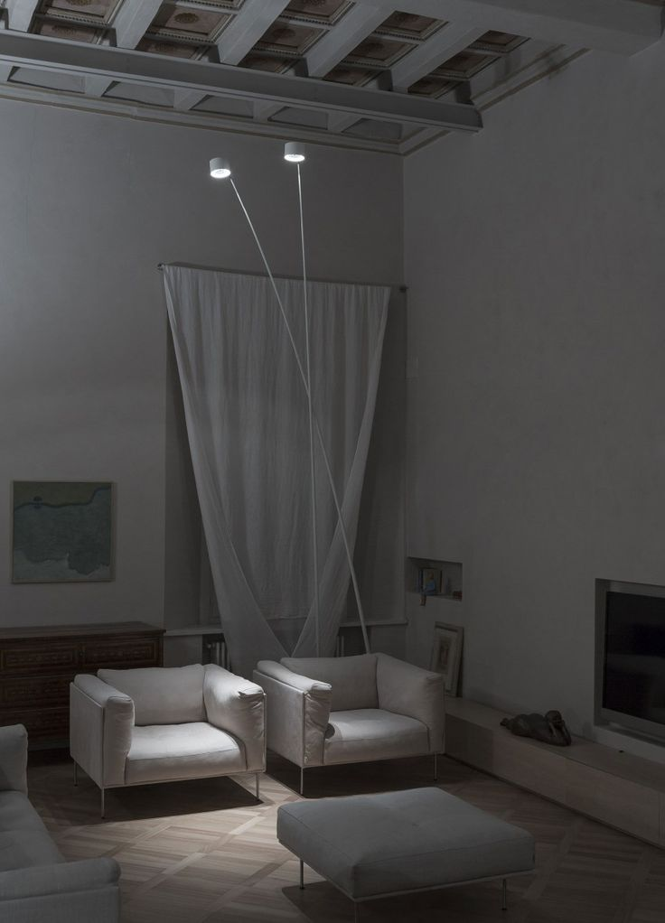 Apartment: Simply Brilliant Apartment In Piacenza Designed by Studio Blesi Subitoni, High Ceiling of Apartment Living Room in Piacenza by Studio Blesi Subitoni showing Drop Ceiling Tile and Tall Arc Floor Lamps and Fabric Arm Chairs and Ottoman