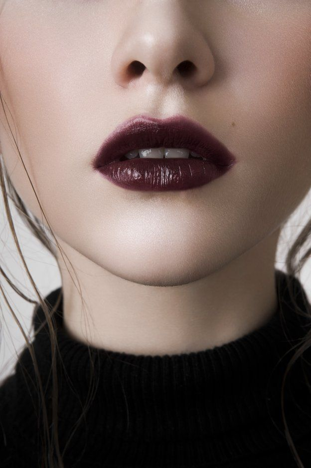 Close-up of woman wearing dark lipstick