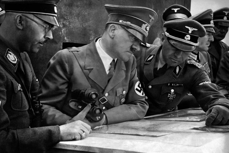 German Chancellor and dictator Adolf Hitler consults a geographical survey map with his general staff including Heinrich Himmler (left) and Martin Bormann (right) at an undisclosed location in 1939.