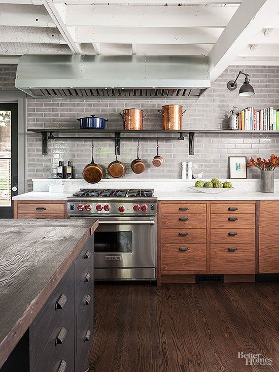 Classic kitchen elements get a new look in the industrial cook space. An elegant tile backsplash feels fresh with a cool gray palette. Rich wood floors and traditional cabinetry warm up modern steely finishes, like a restaurant-style range complete with an oversize hood.