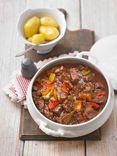 500 g   Rindfleisch, mageres, in 1,5 x 1,5 cm Würfeln    6 m.-große   Zwiebel(n), in grobe Stücke geschnitten    4    Knoblauchzehe(n), in Stücke geschnitten       Rapsöl   1 EL  Paprikapulver, edelsüß   1 EL  Paprikapulver, rosenscharf   3 EL  Tomatenmark   500 ml  Rinderbrühe   3   Paprikaschote(n), rot, gelb, grün, in grobe Stücke geschnitten   125 ml  Rotwein, trockener (nach Belieben)   2 EL  Kümmel, ganz