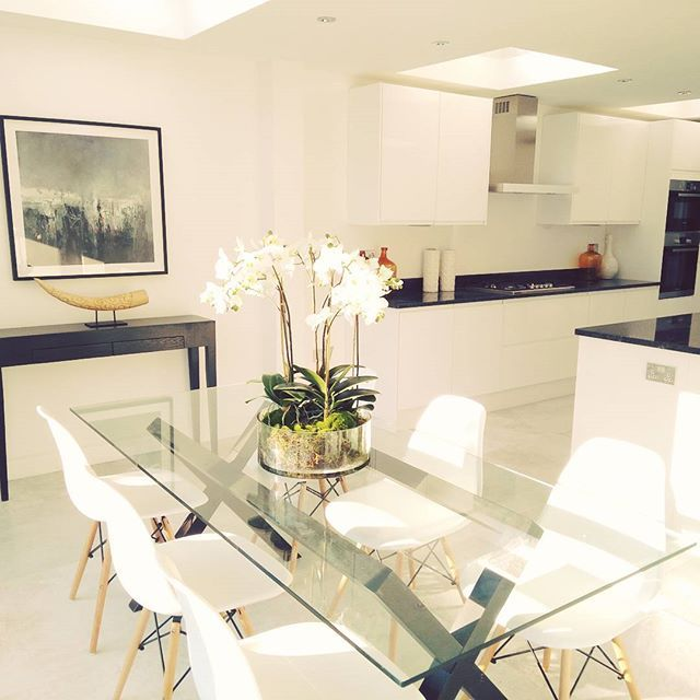 A bright and beautiful kitchen and dining area in a property in Fulham, London. We love using glass tables to keep a room feeling spacious, and Eames chairs are always a classic!