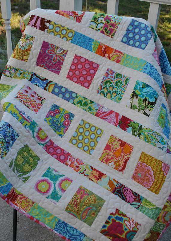 "Bright and simple. Made with Amy Butler's Soul Blossom collection of fabrics, this stunning quilt measures 41"" x 49"". The small squares and rectangles contain one of every 34 prints in the Soul Blossoms collection. I used a cream colored Moda Bella solid for the lattice work between the squares. The backing and binding are made from a the beautiful Passion Lily print from the same line."