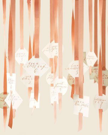 Love the idea of hanging escort card display -- from the trees! Peach ribbon escort cards