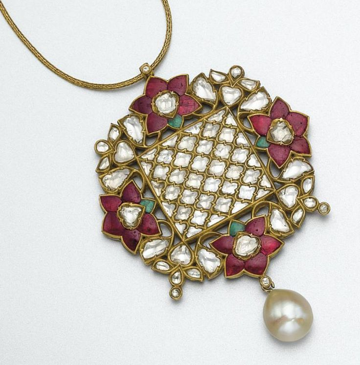 INDIAN GOLD, COLORED STONE AND ENAMEL PENDANT-NECKLACE The modified circular plaque of stylized floral design set on one side with table-cut diamonds and foil-backed rubies and emeralds, the reverse applied with Jaipur enamel in a floral motif, supporting a cultured pearl drop measuring approximately 14.9 by 12.9 mm., mounted in gold, supported on a gold cord chain, length 18 inches.