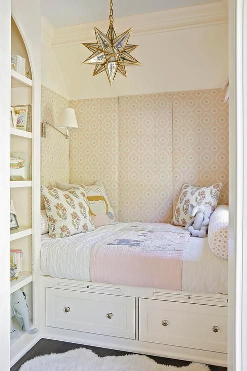 Pink girl's room boasts a nook filled with a built-in bed with drawers dressed in white and pink bedding lined with pink fabric paneled walls illuminated by an antiqued mirrored Moravian pendant by Serena & Lily placed next to an arched bookcase.