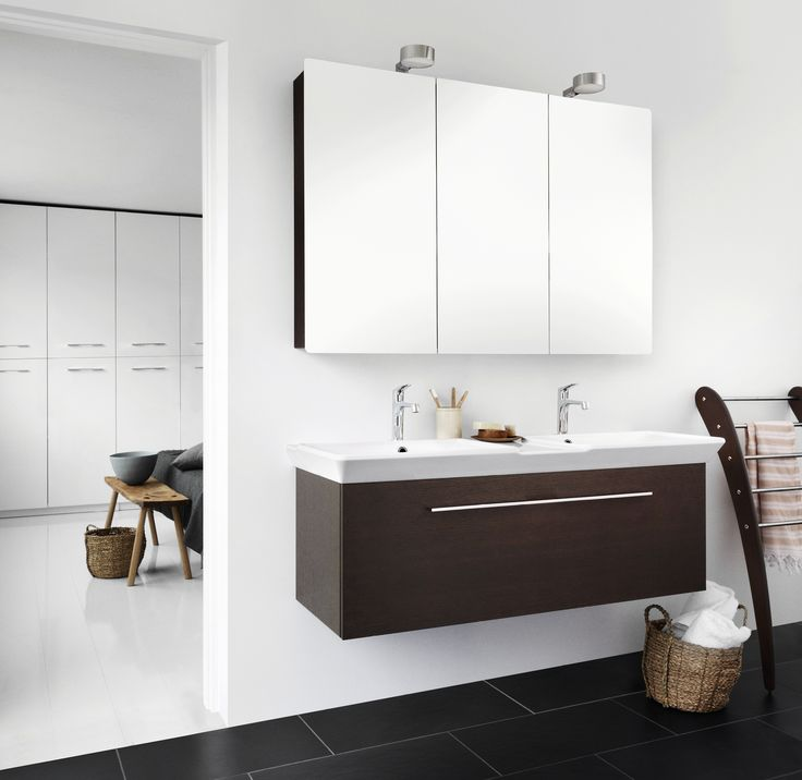 Why not open up between the bathroom and the bedroom? Calidris cabinets in the bedroom and dark oak with double washbasin and mirror cabinets in the bathroom create an exclusive and expressive whole.