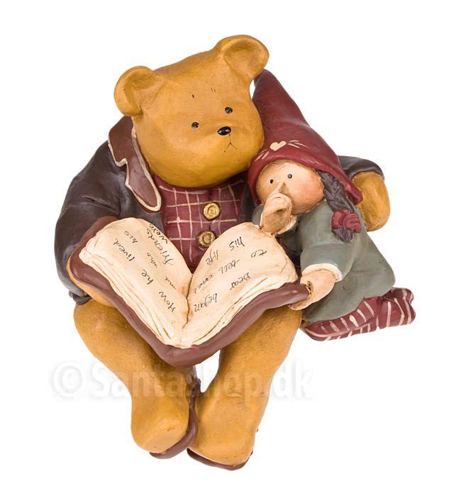 Denne store skønne bjørn med bogen og nissen skal sidde på kanten af en reol eller bord. Figuren vejer omkring 600 gram. Stemplet med det originale Annekabouke stempel. Højde: 11 cm. Dybde: 11 cm. Materiale: Polysten. Bjørnen leveres i æske udformet som en dagbog, der lukkes med silkebånd, og æsken er fyldt med polstring, så bjørnen ligger fast og sikkert. Egner sig meget fint til forsendelse.