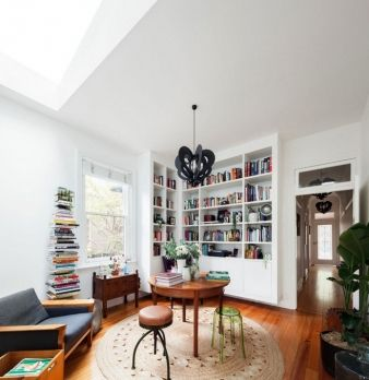 A large shelf occupies a corner of the study area, which is illuminated by a skylight