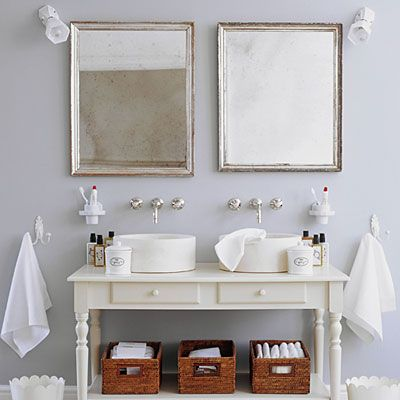 Scour local flea markets for furniture you can convert into a sink console, such as the vintage table seen here. Large hooks are an economical alternative to towel bars that look just as nice when they're holding colorful towels. Instead of a medicine chest, opt for ordinary wall mirrors; toiletries, extra towels and other sundry items can be stored in plastic or wicker baskets.