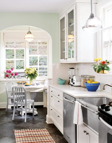 white cabinets, seaglass green walls, with industrial stainless (plus breakfast room chairs!) from Country Living