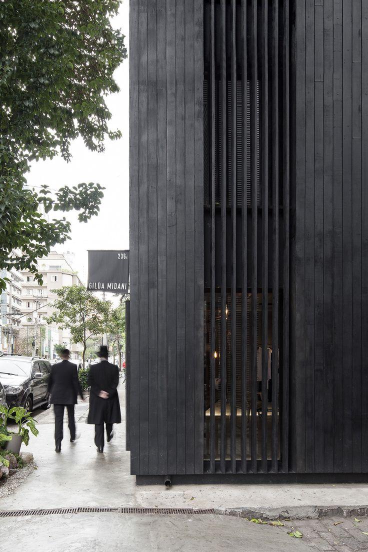 O interior desta loja em São Paulo foi todo trabalhado em concreto aparente. As fachadas foram revestidas em tábuas e brises de madeira carbonizada.