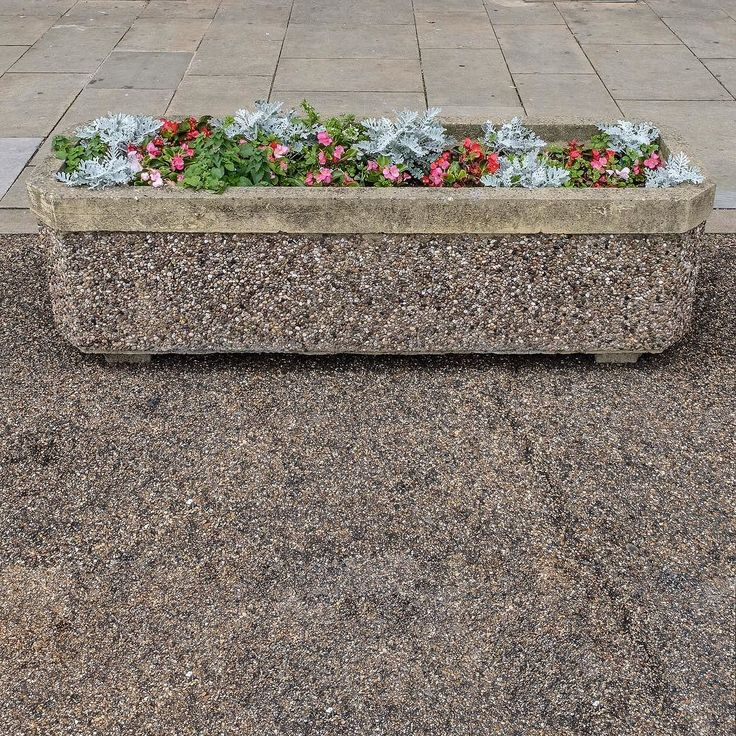 A camouflaged pebble dashed planter.